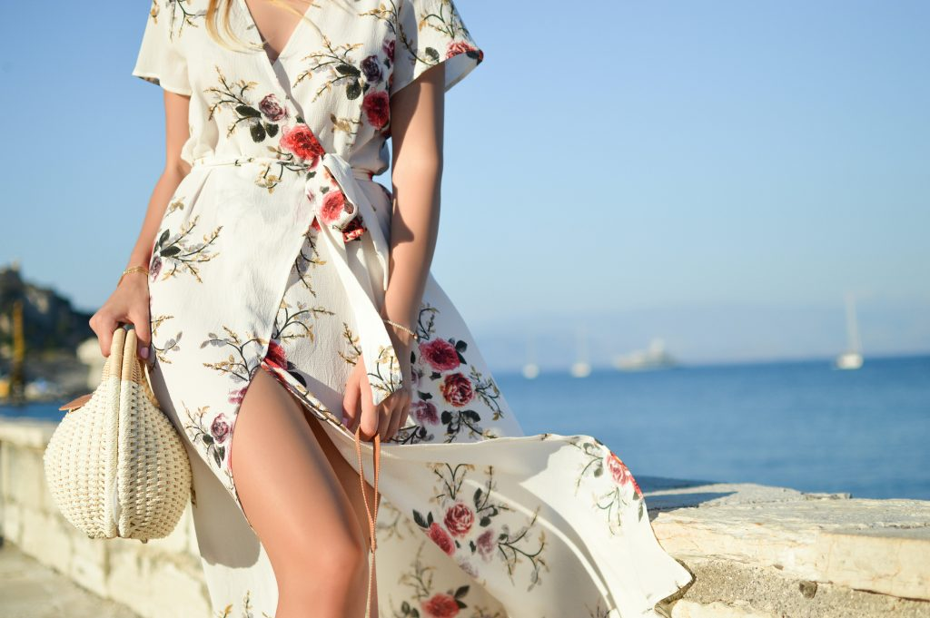 closeup of woman in white floral wrap dress walking along shore